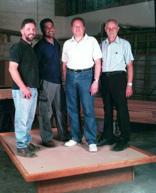 four men standing on our floating platform bed